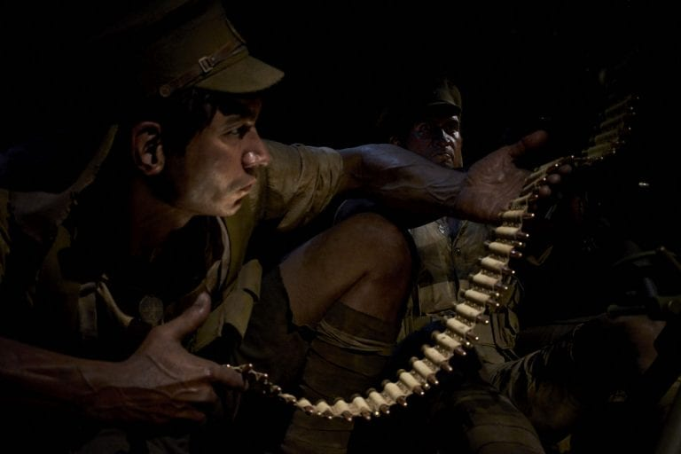 Image of a larger than life size sculpture of a soldier loading magazine clips into a machine gun during the Gallipoli campaign in WWI housed at Te Papa Museum in Wellington