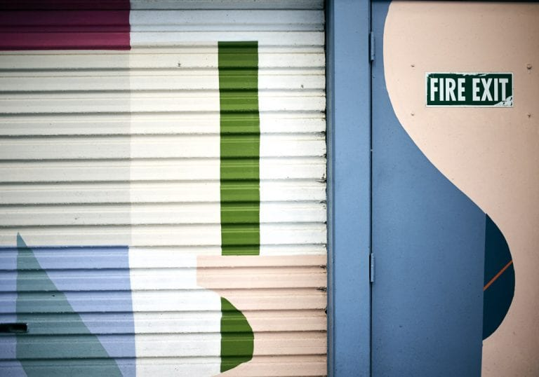 Street art mural of a brightly coloured geometric patterns on a garage door in the laneway of Egmont Street in Wellington