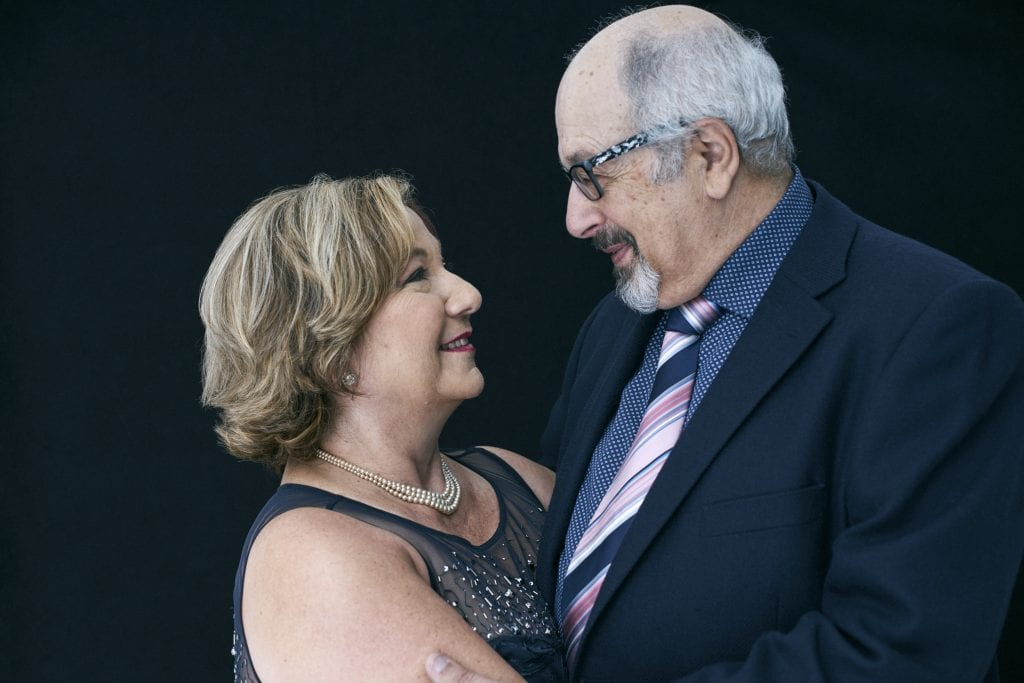 Studio portrait of an older couple both in smart clothing hugging and smiling at each other by Vancouver contemporary portrait photographer Angela McConnell