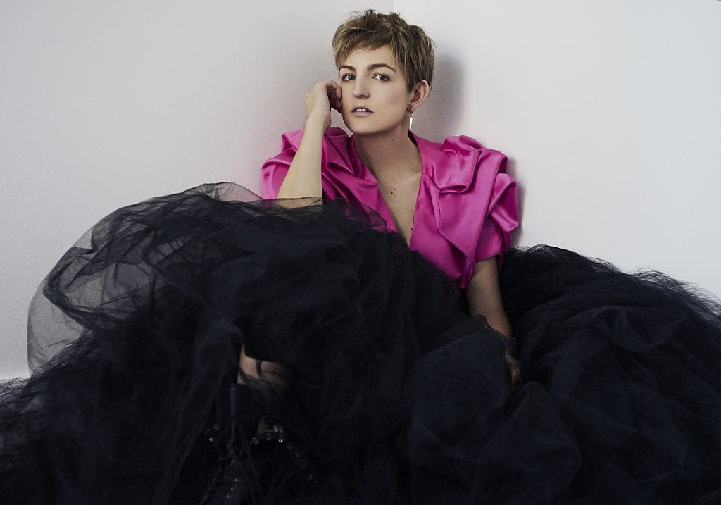 Natural light portrait portrait of an aussie actress wearing a structural pink crop jacket and large black tulle skirt with combat boots looking directly at the camera by Vancouver contemporary portrait photographer Angela McConnell