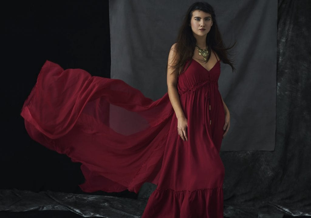 Studio portrait of a young woman wearing a red boho dress and with long hair blowing away from her face by Vancouver contemporary portrait photographer Angela McConnell