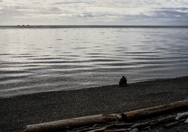 Image of a man and young boy huddled together at the shoreline on a pebble and log strewn beach at Sechelt on the Sunshine Coast, BC