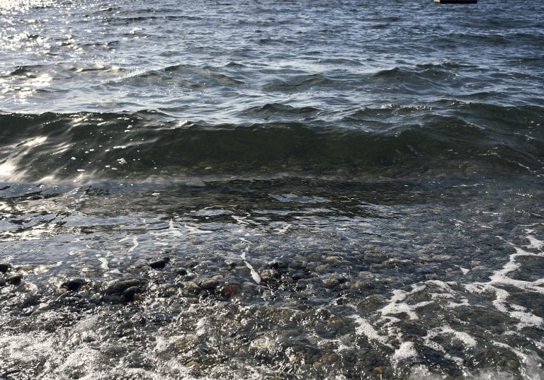Image of a wave coming towards the shoreline with water so clear you can see the pebbles on the seabed at Sechelt on the Sunshine Coast, BC