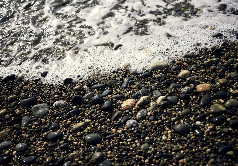 Image of the sun shining on wet pebbles as waves roll in on a beach in Sechelt on the Sunshine Coast, BC
