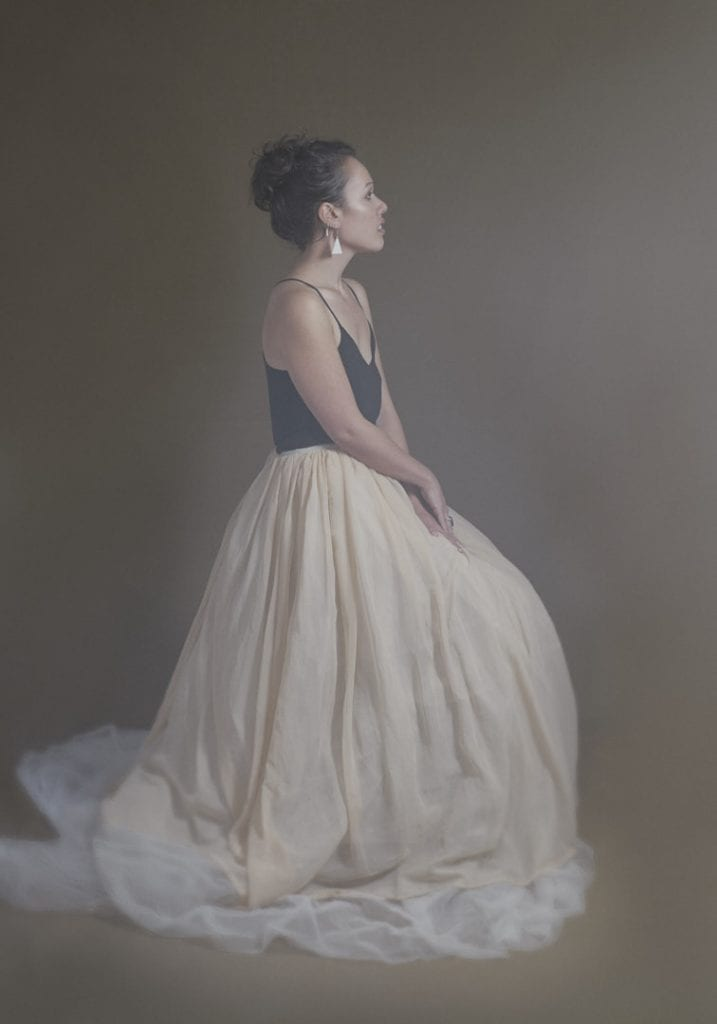 Studio portrait of a young Maori woman in a large tulle skirt posing in profile during a session where kiwi expats come together by Vancouver contemporary portrait photographer Angela McConnell