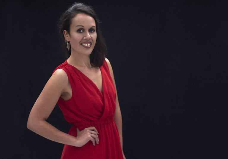 Studio portrait of a young Maori woman in a red dress smiling at the camera during a session where kiwi expats come together by Vancouver contemporary portrait photographer Angela McConnell