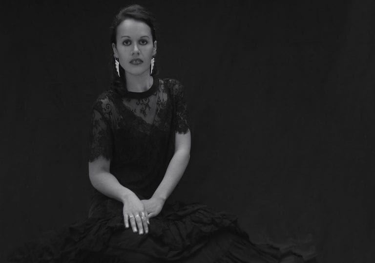 Black and white studio portrait of a young Maori woman in a black dress and lace top looking at the camera during a session where kiwi expats come together by Vancouver contemporary portrait photographer Angela McConnell