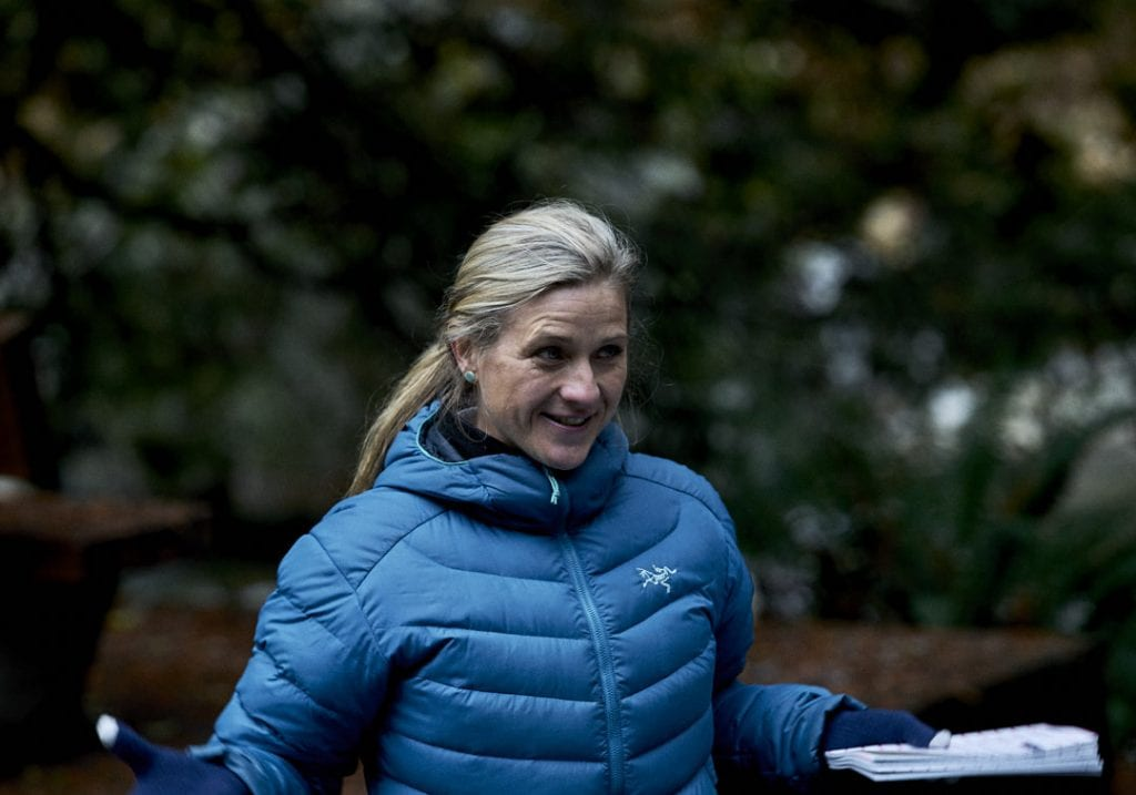 A workshop facilitator in a blue puffer jacket speaks to attendees while running a coaching session during a self care and fitness workshop by Vancouver workshop and retreat photographer Angela McConnell