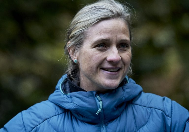 A workshop facilitator in a blue puffer jacket smiles at attendees in a coaching session during a self care and fitness workshop by Vancouver workshop and retreat photographer Angela McConnell