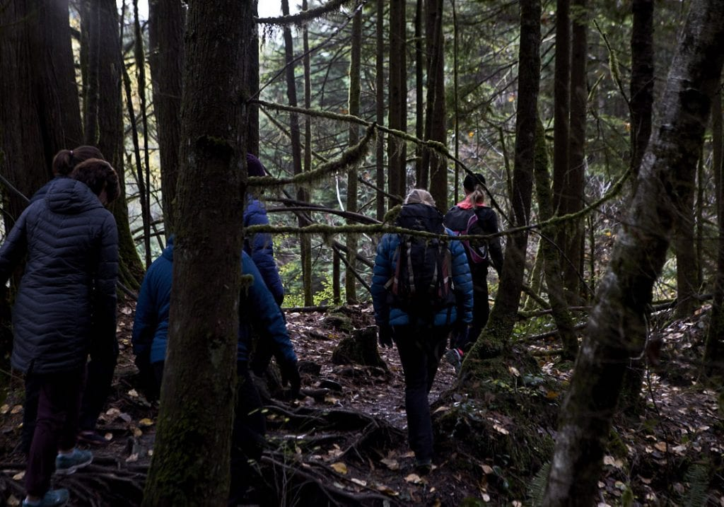 Women with backpacks walking through a forest path surrounded by trees covered in hanging moss during a self care and fitness workshop by Vancouver workshop and retreat photographer Angela McConnell