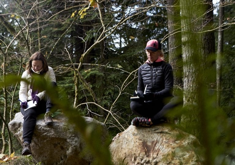 Two women writing in journals during a coaching session at a self care and fitness workshop by Vancouver workshop and retreat photographer Angela McConnell