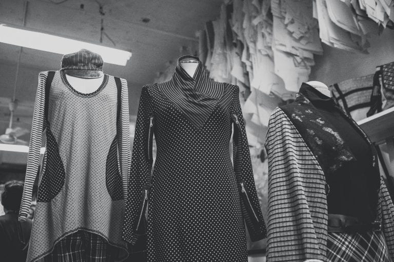 Black and white image of local designers cloths on a mannequins with pattern hanging from the ceiling in the background