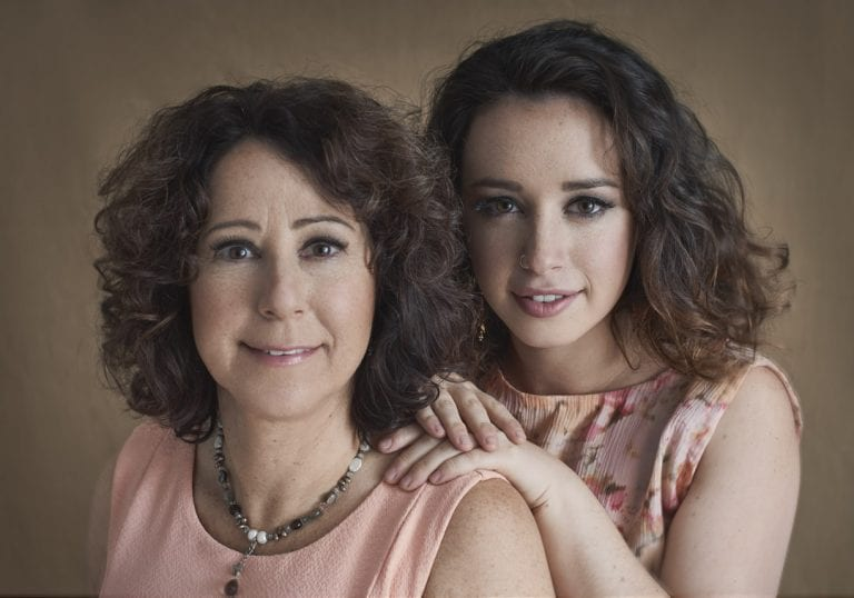 Studio portrait of a young woman resting her hands on her mothers shoulder as they both look and smile at the camera for portraits with Mum by Vancouver contemporary portrait photographer Angela McConnell