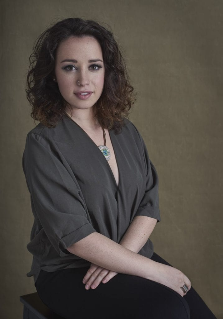Studio portrait of a young woman with curly brown hair wearing a statement necklace resting her hands in her lap and smiling at the camera for portraits with Mum by Vancouver contemporary portrait photographer Angela McConnell
