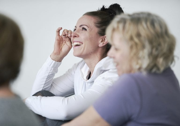 A woman wipes tears away as she laughs while sharing in a group of women at a mothers and daughters workshop in Vancouver focusing on relationships and self care by Vancouver workshop and retreat photographer Angela McConnell