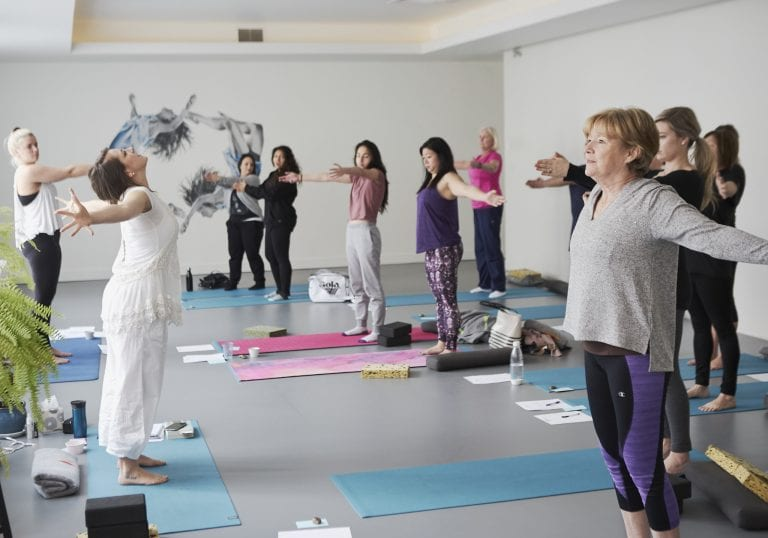 A woman dressed in white leading a yoga exercise for a group of women at a mothers and daughters workshop in Vancouver focusing on relationships and self care by Vancouver workshop and retreat photographer Angela McConnell