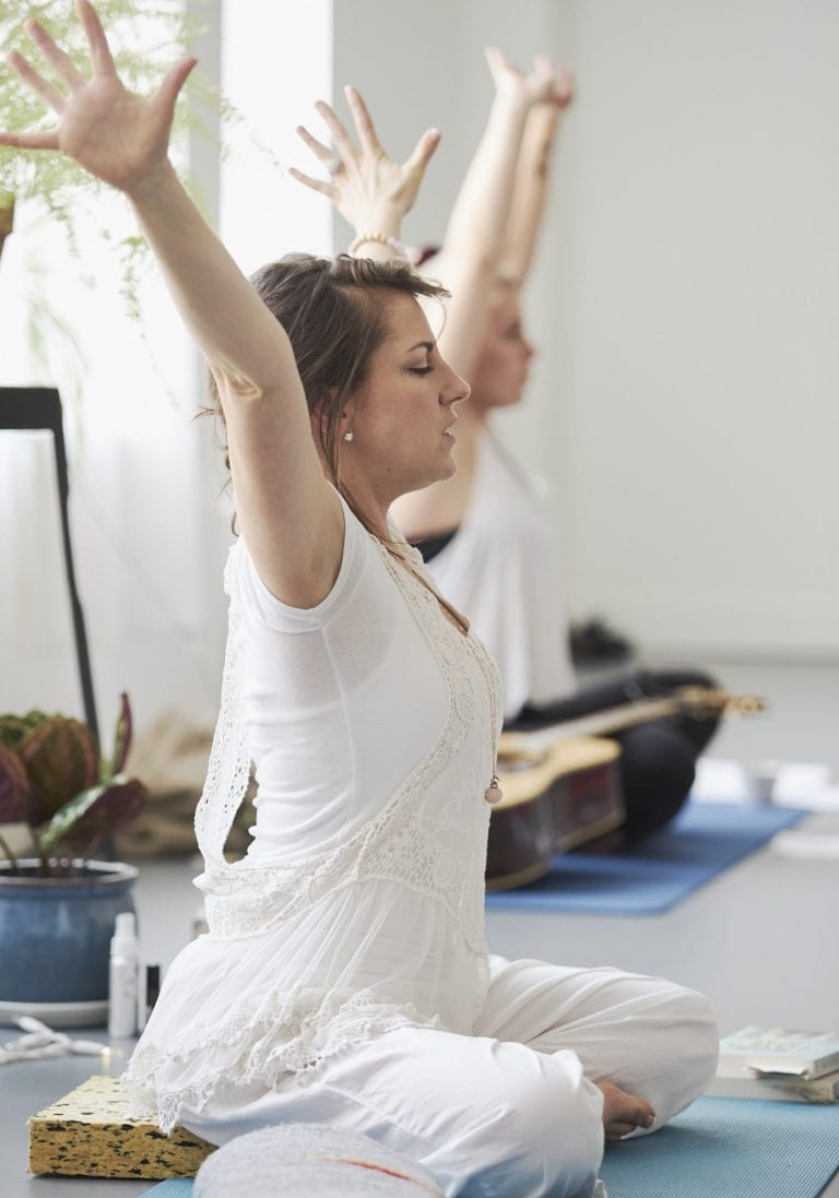 A woman dressed in white sitting on a yoga mat directing a group of women at a mothers and daughters workshop in Vancouver focusing on relationships and self care by Vancouver workshop and retreat photographer Angela McConnell