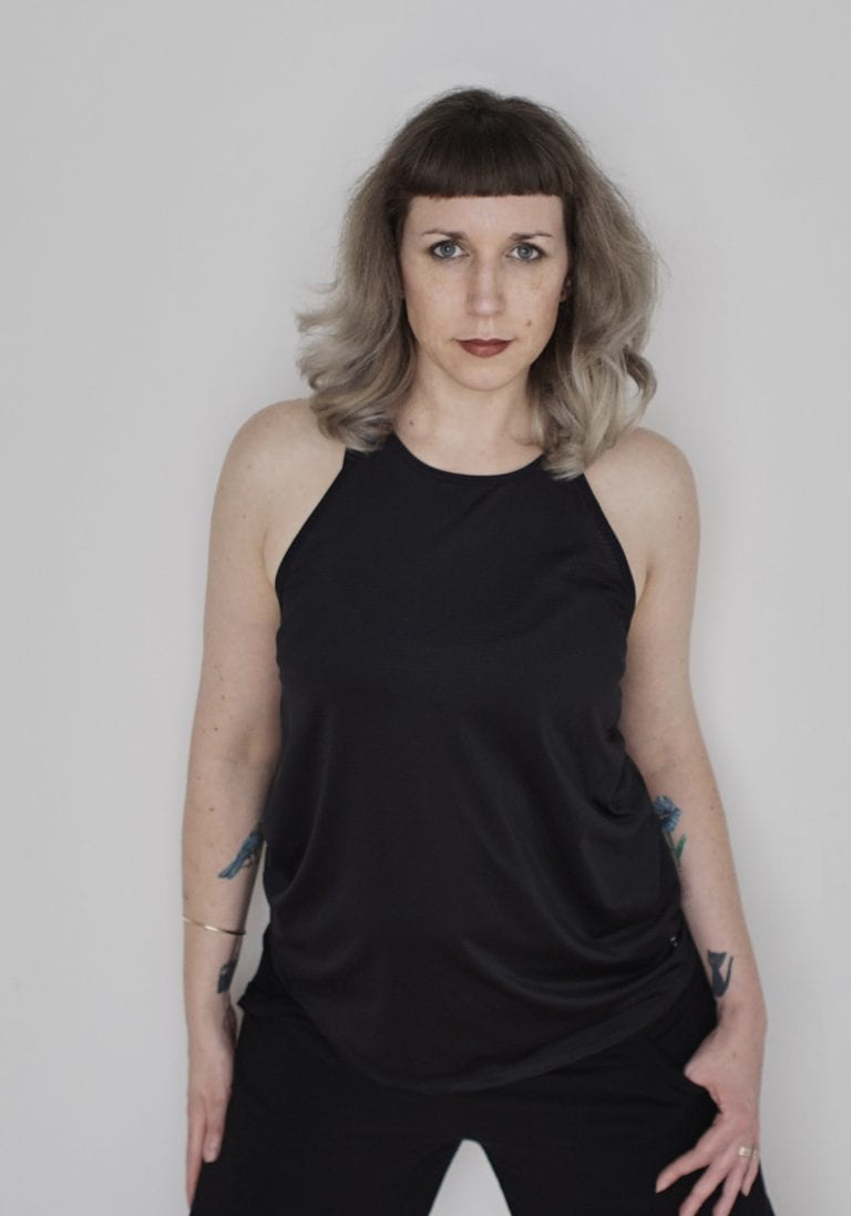 Birthday self portrait of a woman with silver hair and tattoos on her inner forearms wearing black posing and smiling at the camera by Vancouver contemporary portrait photographer Angela McConnell