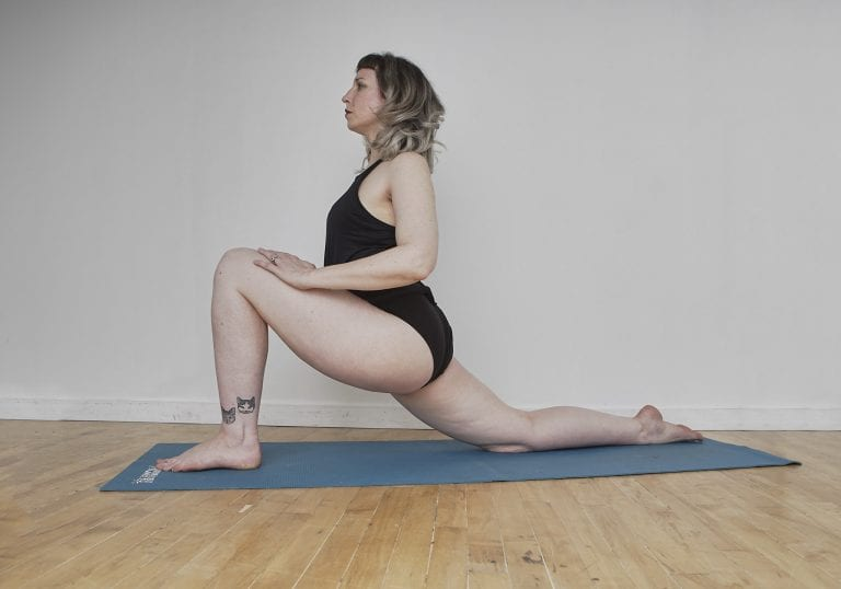 Birthday self portrait of a woman with silver hair and tattoos doing a low lunge pose on a blue yoga mat by Vancouver contemporary portrait photographer Angela McConnell