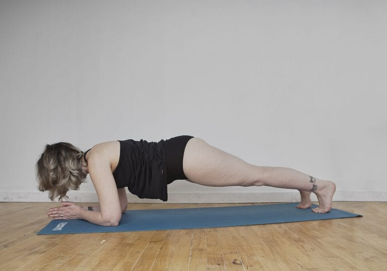 Birthday self portrait of a woman with silver hair and tattoos doing low plank pose on a blue yoga mat by Vancouver contemporary portrait photographer Angela McConnell