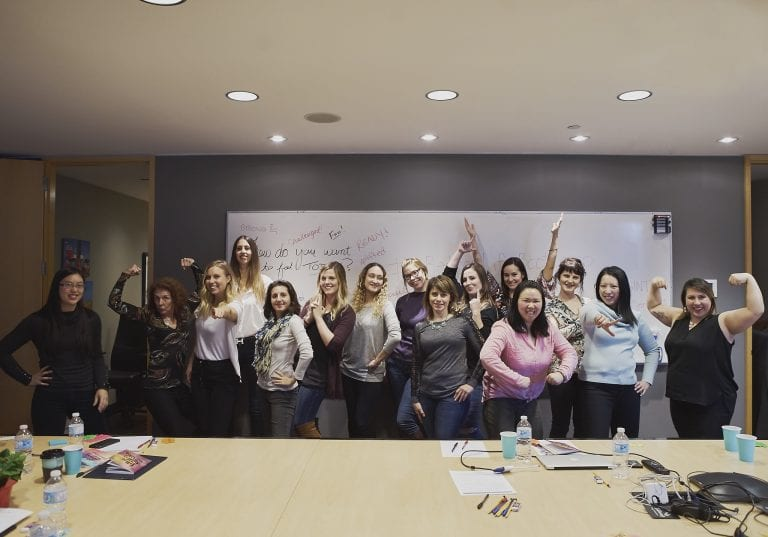 Image of a group of women in power poses in front of a whiteboard with empowering phrases during a self care workshop by Vancouver workshop and retreat photographer Angela McConnell