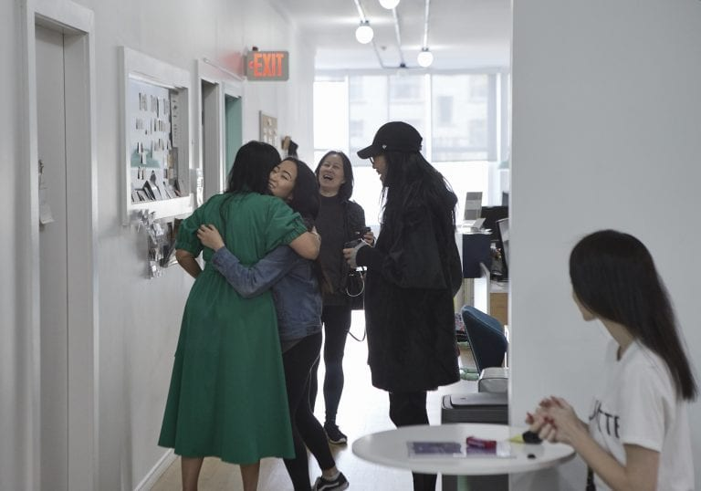 A woman in an emerald green dress greeting other women with hugs before the start of a self care and confidence workshop by Vancouver workshop and retreat photographer Angela McConnell