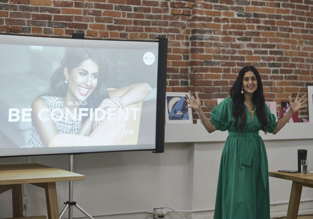 Woman in an emerald green dress talks to attendees with a projection screen with Confidence and a smiling women in the background during an exercise at a self care and confidence workshop by Vancouver workshop and retreat photographer Angela McConnell