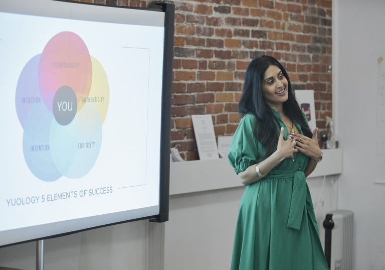 Woman in an emerald green dress smiles as she talks to attendees in front of a projection screen with the 5 elements of success on it at a self care and confidence workshop by Vancouver workshop and retreat photographer Angela McConnell