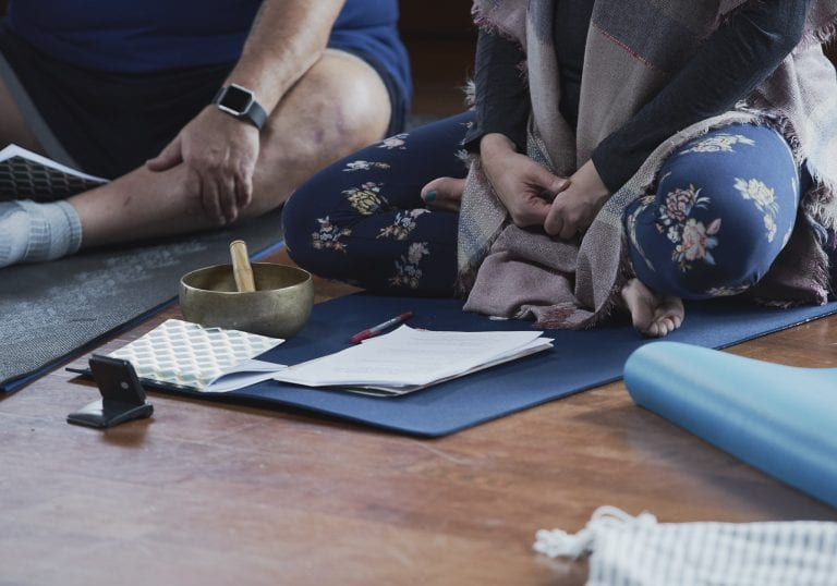 A facilitator sits cross legged on a blue yoga mat with course notes and a tibetan singing bowl in front of her during a self care for educators workshop at Roundhouse Farm, Victoria BC by Vancouver workshop and retreat photographer Angela McConnell