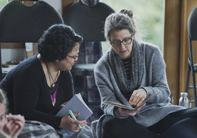 Two women sitting on the floor lean into each other to compare notes during a group exercise at a self care for educators workshop at Roundhouse Farm, Victoria BC by Vancouver workshop and retreat photographer Angela McConnell