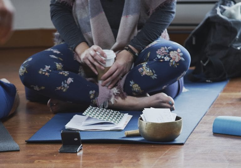 A tibetan singing bowl is filled with addressed envelops on a blue yoga mat where the facilitator sits cross legged at a self care for educators workshop at Roundhouse Farm, Victoria BC by Vancouver workshop and retreat photographer Angela McConnell