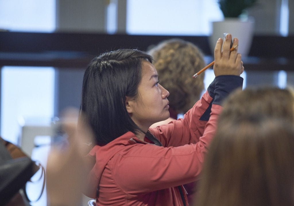 Woman holds up a mobile phone to take a picture at a women in male dominated industries event by Vancouver business portrait and branding photographer Angela McConnell