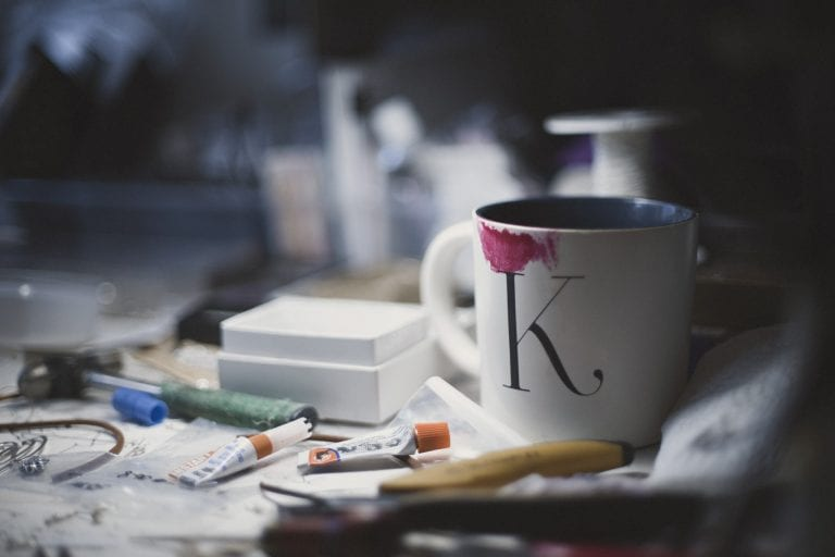 Photo of a white coffee cup with red lipstick stain on a jewellery designers desk by Vancouver business portrait and branding photographer Angela McConnell