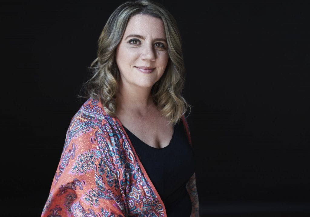 Natural light business portrait of a woman in a coloured top smiling at the camera by Vancouver business portrait and branding photographer Angela McConnell