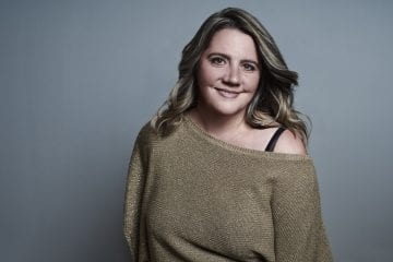 Studio business portrait of a woman in a gold jumper smiling at the camera by Vancouver business portrait and branding photographer Angela McConnell