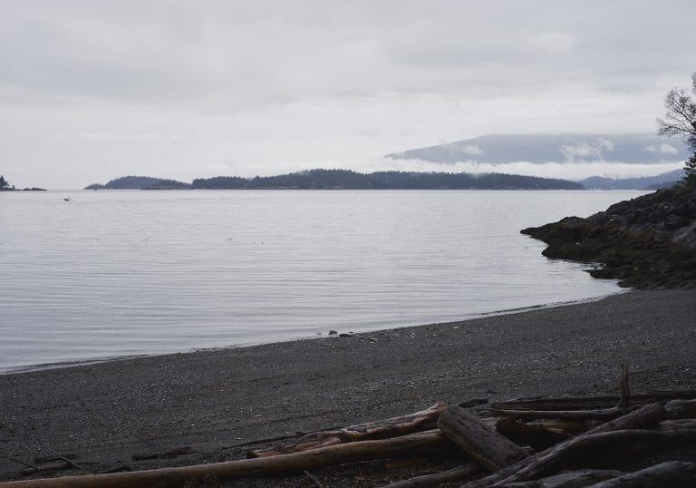 View of the sea and surrounding islands with a small boat on the water at at Pebbly Beach during a Thanksgiving getaway on Bowen Island