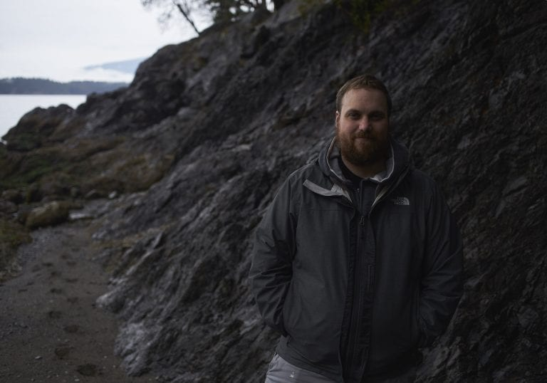 Portrait of a man standing in front of a stark rock face at Pebbly Beach during a Thanksgiving getaway on Bowen Island