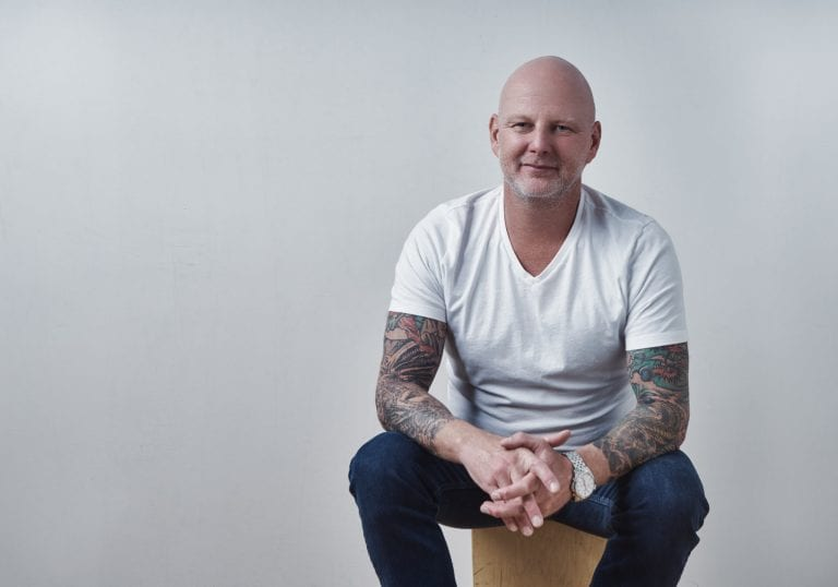Man in a white tshirt and jeans with full sleeve tattoos smiles at the camera during a life coach branding session with Vancouver business portrait and branding photographer Angela McConnell