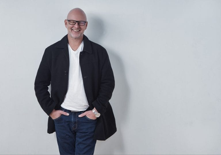 Man in a white tshirt, jeans and woolen coat smiles at the camera during a life coach branding session with Vancouver business portrait and branding photographer Angela McConnell