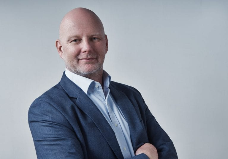 Man in a blue shirt suit jacket smiles at the camera during a life coach branding session with Vancouver business portrait and branding photographer Angela McConnell