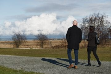 A man and a woman walk together during a coach and walk session by leadership coach David Lundberg from Small Pause Coaching by Vancouver business and branding photographer Angela McConnell