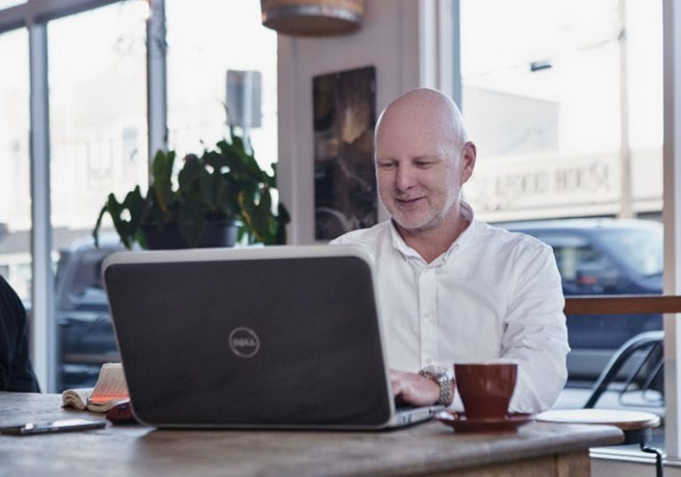 Leadership coach David Lundberg from Small Pause Coaching works on his laptop in a cafe in Steveston by Vancouver business and branding photographer Angela McConnell