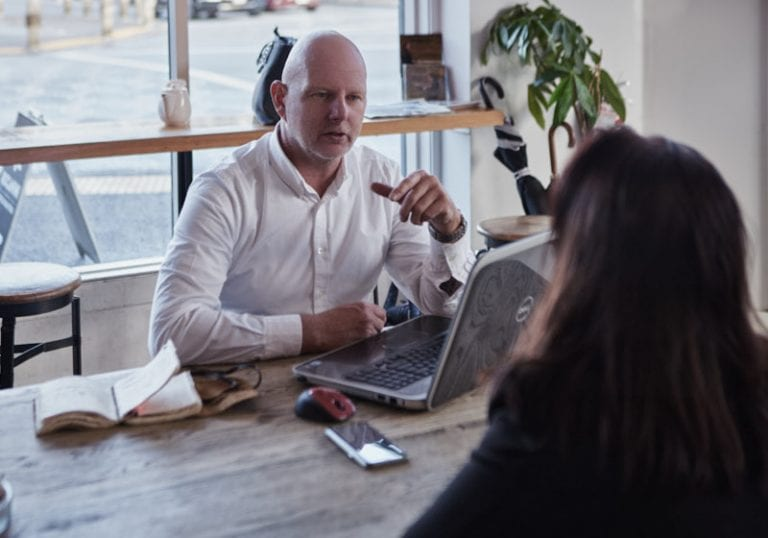 A man and a woman talk in cafe together during a coaching session with leadership coach David Lundberg from Small Pause Coaching by Vancouver business and branding photographer Angela McConnell