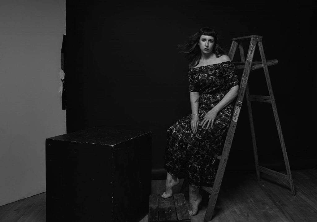 Black and white 40th birthday self portrait photography with a woman posing with a ladder and looking at the camera by Vancouver contemporary portrait photographer Angela McConnell