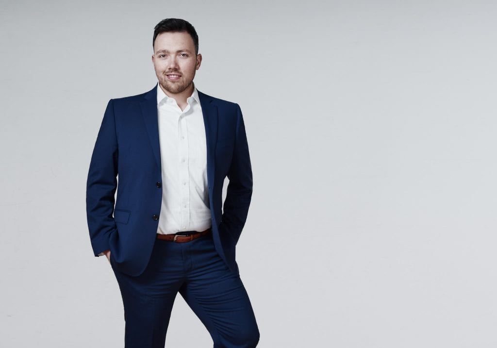 A man in a blue suit stands with his hands in his pockets and smiles at the camera by Vancouver business portrait and branding photographer Angela McConnell