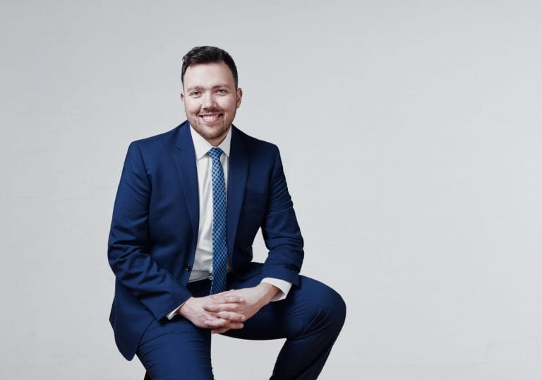 A man in a blue suit sits with his hands clasped and smiles at the camera by Vancouver business portrait and branding photographer Angela McConnell