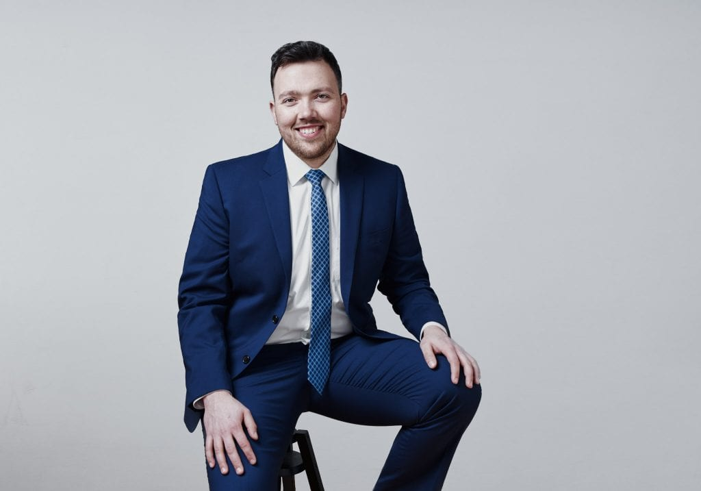 A man in a blue suit sits and smiles at the camera by Vancouver business portrait and branding photographer Angela McConnell