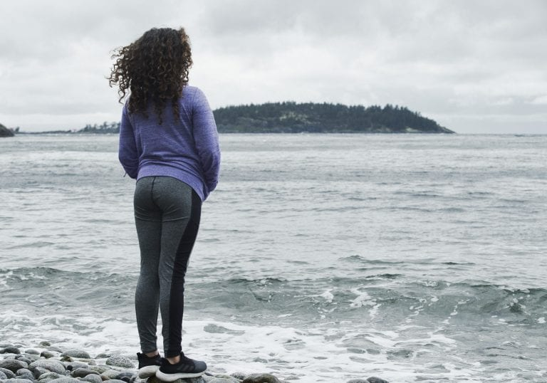 A young girls stands looking over the water on a pebble beach at Halfmoon Haven in Sechelt BC