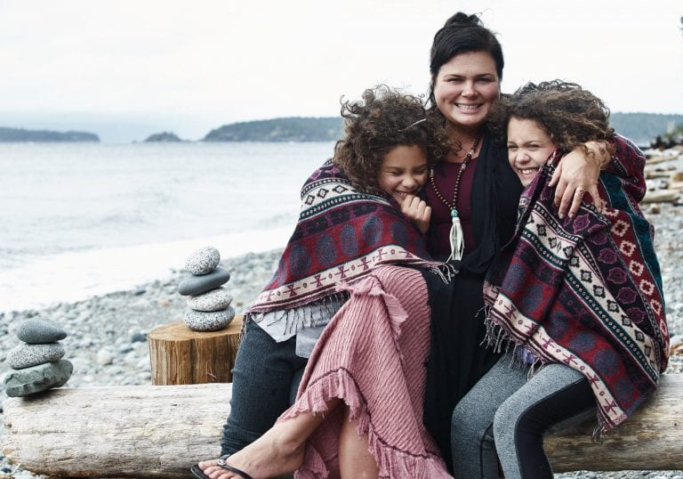 A mother and her daughters hug during portraits on a beach at a mother and daughter workshop by Vancouver workshop and retreat photographer Angela McConnell