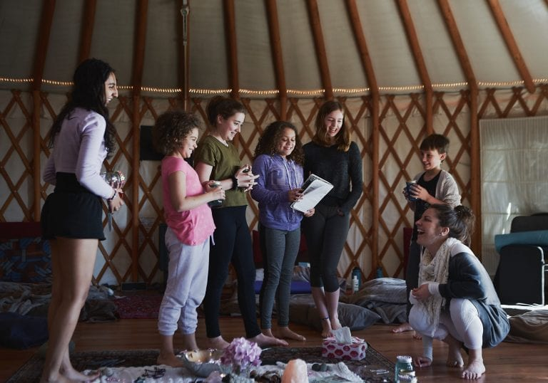 Girls present a project to a facilitator as she smiles at a mother and daughter workshop by Vancouver workshop and retreat photographer Angela McConnell